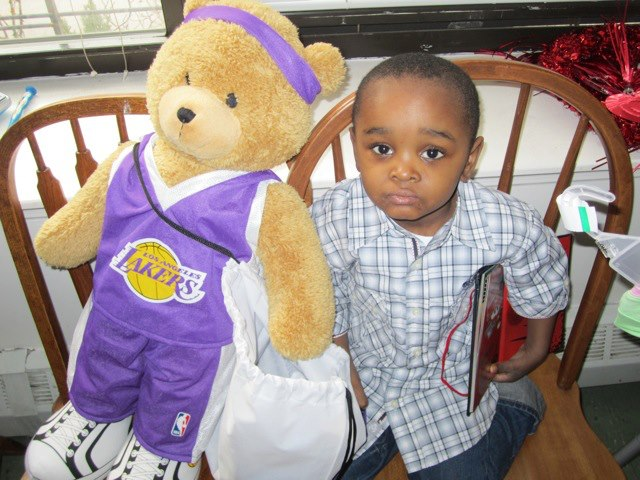 Child at comfort Drop holding LA Lakers Bear